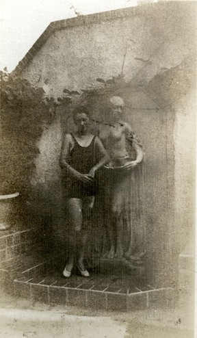 <em>Unidentified woman standing by the fountain in the garden on the south side of the Byrne-Reed House. Courtesy of the Reed family.</em>