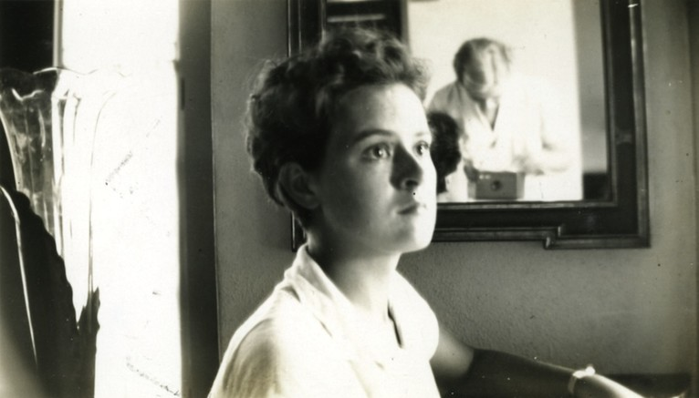 <em>Ruth Reed, reflected in mirror, takes a photograph of a friend. Courtesy of the Reed family.</em>
